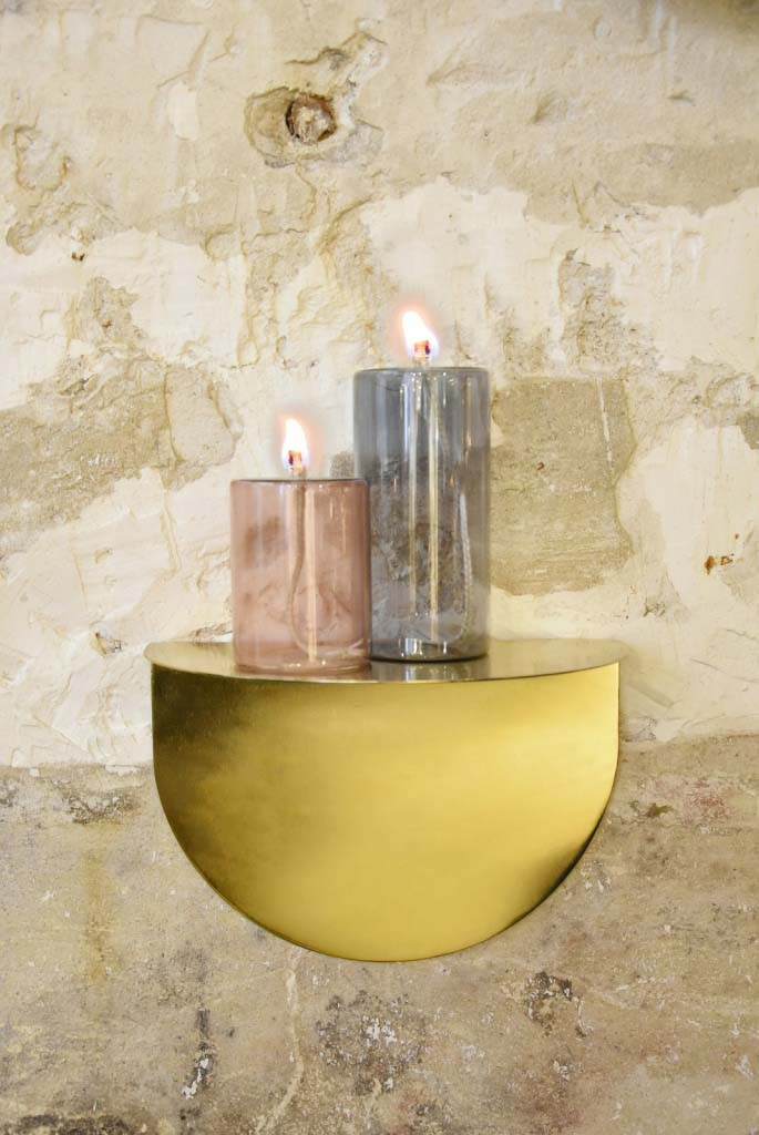 A small brass table stand (like a shelf) with colored glass lanterns atop against a concrete wall