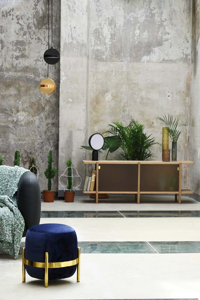 Partial view of a sofa with a dark blue velvet pouf on a brass stand in the foreground. At the background a sideboard with decor against a concrete wall is shown