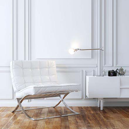 stylish white leather Barcelona armchair in minimal interior design with a white sideboard on the right and hardwood floors