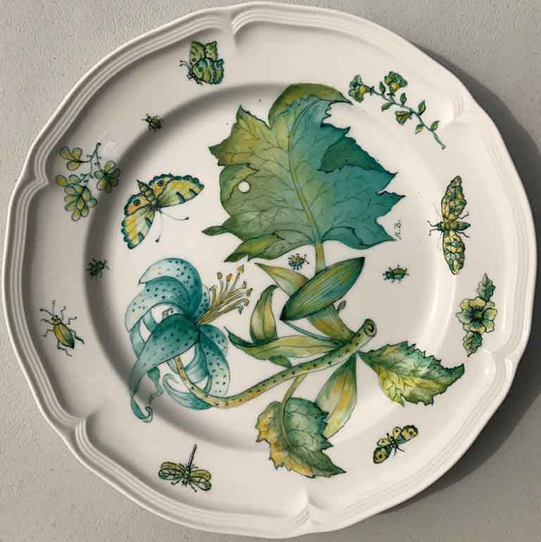 A dinner plate with a blue flower and lots of complimentary leaves and green bugs drawn on it