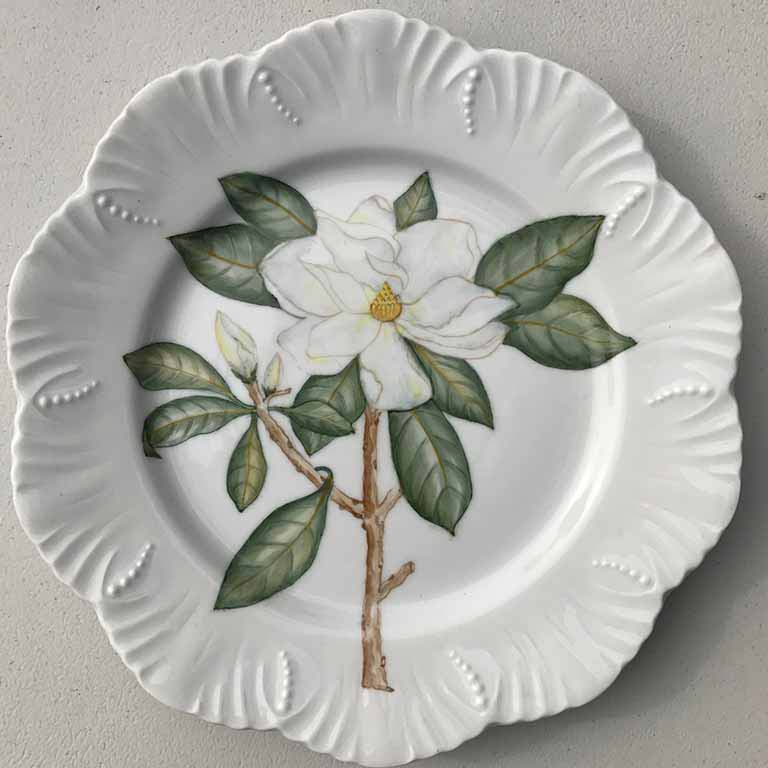 A white plate with a large white flower drawn on it