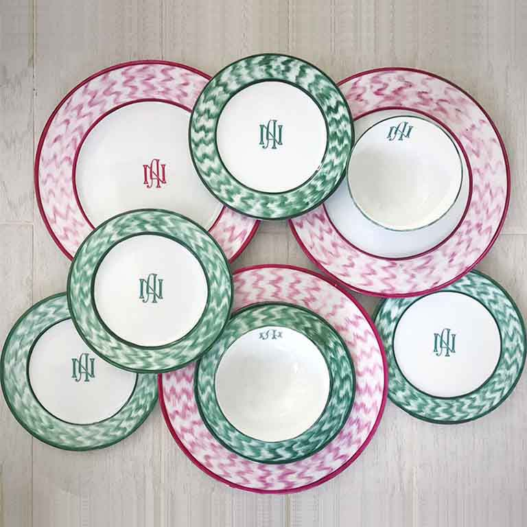 An assortment of plates in various sizes painted either with a dark print pattern or an emerald green one