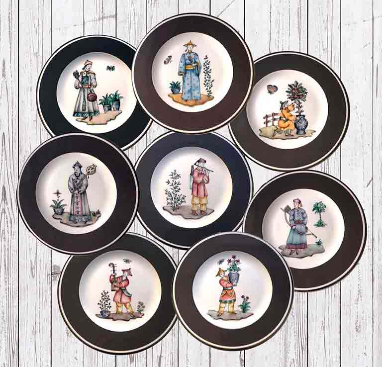 A group of plates with Chinese figures and a dark thick band around their trim