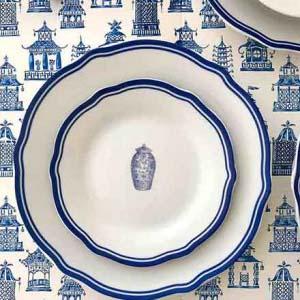 A set of porcelain dinnerware with indigo blue trim and a discrete design in the center