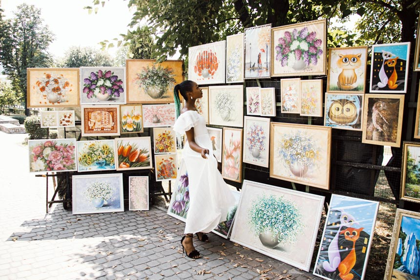 A beautiful black woman looking at some artwork on display somewhere outdoors.