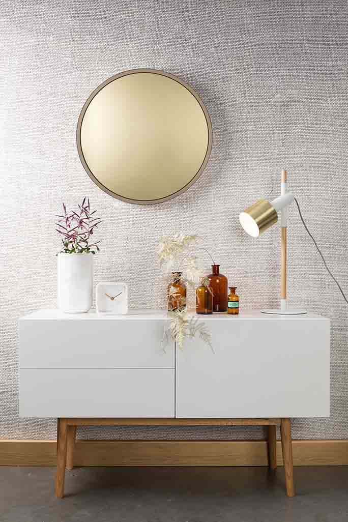 A brass round mirror over a white sideboard is ideal and totally trendy. A brass table lamp, a cluster of colored glass vases and some florals and voila - the perfect ensemble! Image from Cuckooland.com