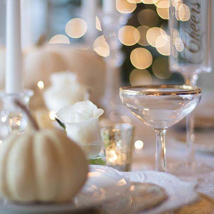 Detail image of a Thanksgiving place setting with a small white pumpkin on a white china plate