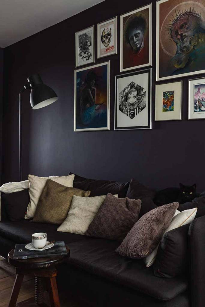 A moody living room with a dark puple wall and an art gallery hang really high.