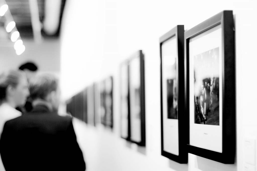 A black and white image of people viewing artistic photo images in an exhibition