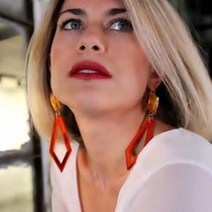 A young blonde woman with long geometric statement earrings