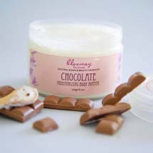 A chocolate body butter product with pieces of chocolate bars next to it