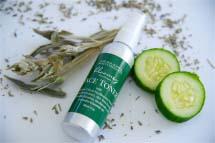 A facial toner spray mist next to slices of cucumber