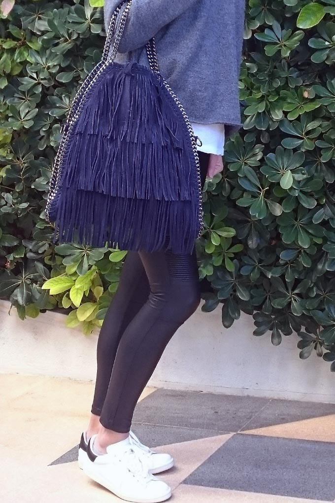 Velvet wearing white Stan Smith's, black faux leather leggings, a grey sweater and carrying a blue fringed bag.