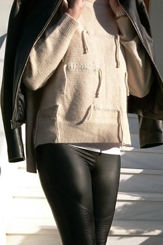 A knitted top paired with faux leather leggings and a black leather biker's jacket.