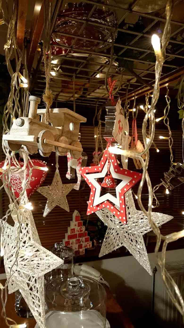 A close up image of the Christmas decor hanging from a pot rack (including a toy train, hearts and lot of stars).