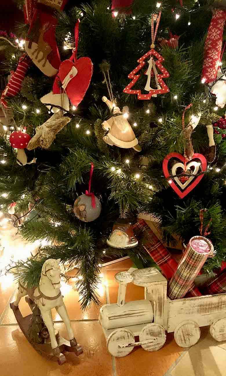 Close up of Elisabeth's Christmas tree with red and beige decor hanging from it and a wooden off white rocking horse decor to the left and a toy tray with gift wrapping paper inside it. Image by Velvet for Te Esse.