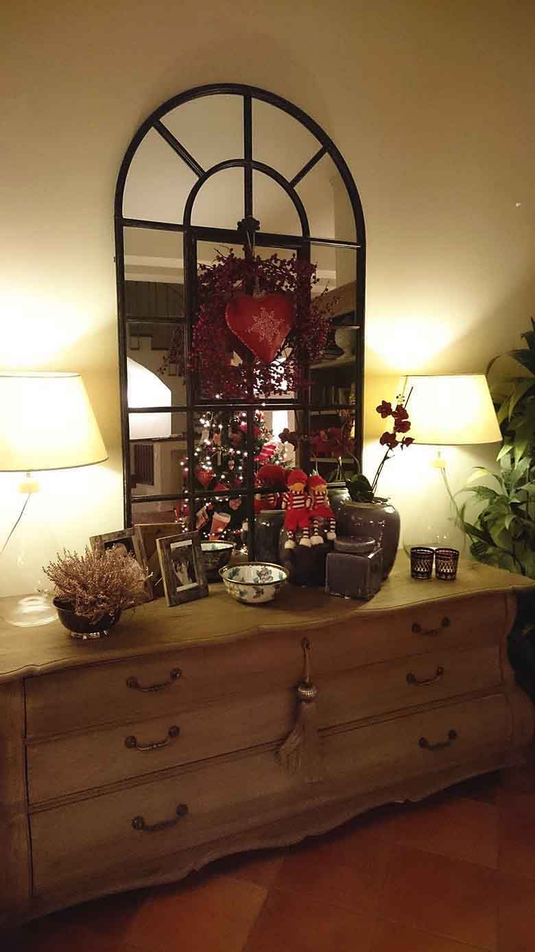A large ash wooden sideboard (cottage styled) with two table lamps on either side, picture frames, decor and planters create a beautiful vignette. A black framed large mirror rests atop, decorated with a holly berry wreath and a heart in the middle.