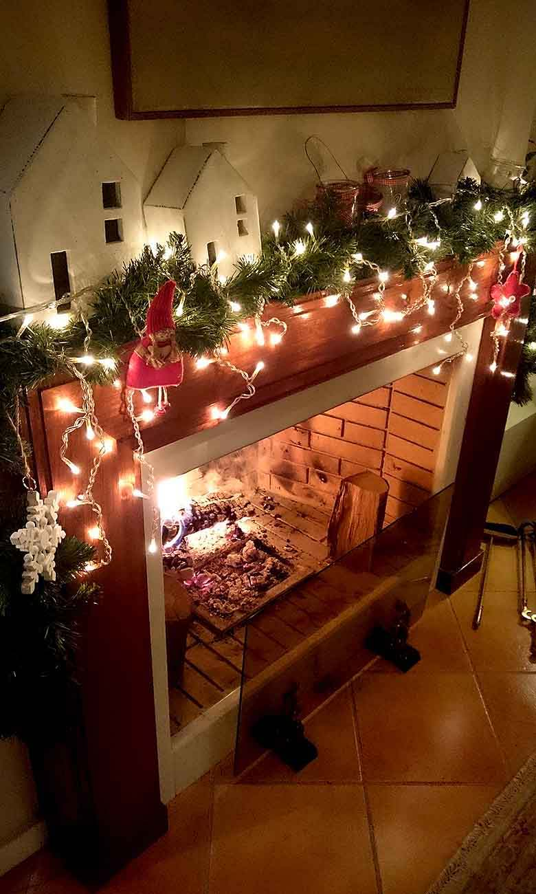 View of Elisabeth's fireplace with a fire going in it, and plenty of Christmas decor on the mantel creating a very cozy vignette. Led lights illuminate the fake pine garland and the ceramic white decor houses resting on either end of the mantel. Image by Velvet for Te Esse.
