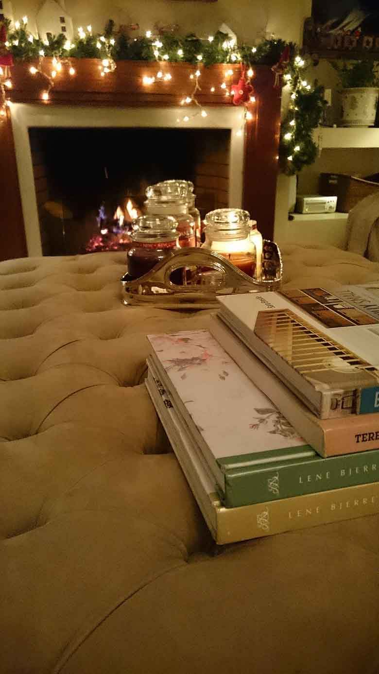 In the background view of Elisabeth's fireplace with a fire going and lots of Christmas decor on the mantel. In the foreground, a stack of books on a large beige velvet ottoman and a tray filled with burning Yankee scented candles.