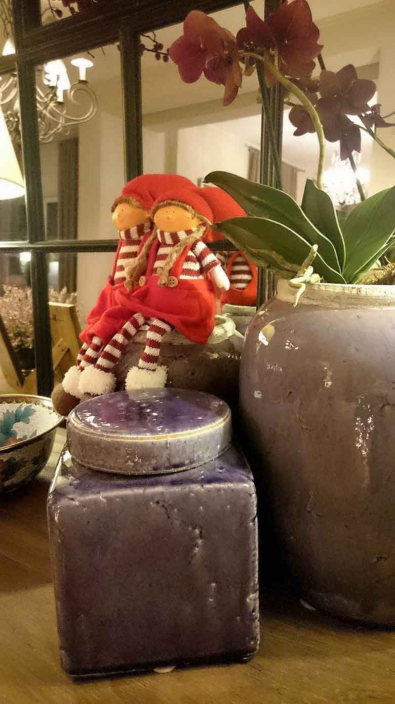 A close up view of two little child like figurines decor dressed in red outfits, placed a top a cluster of purple planters on Elisabeth's sideboard. Behind them, a large black framed mirror.