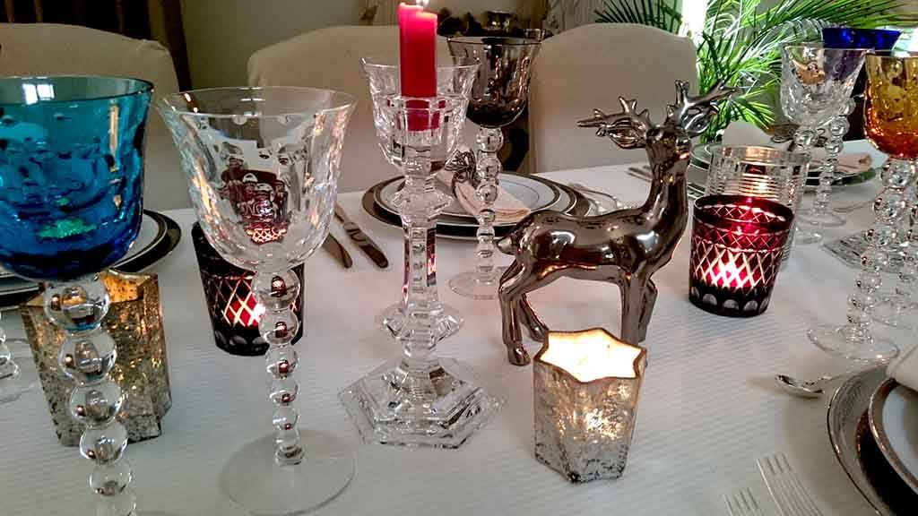 A beautifully styled tabletop for a New Year's Eve dinner party with lots of colored wine glasses, white porcelain plates with silver trims, silver cutlery all on a white tablecloth. Detail view of the candles and silverish reindeer figurines used as decor.