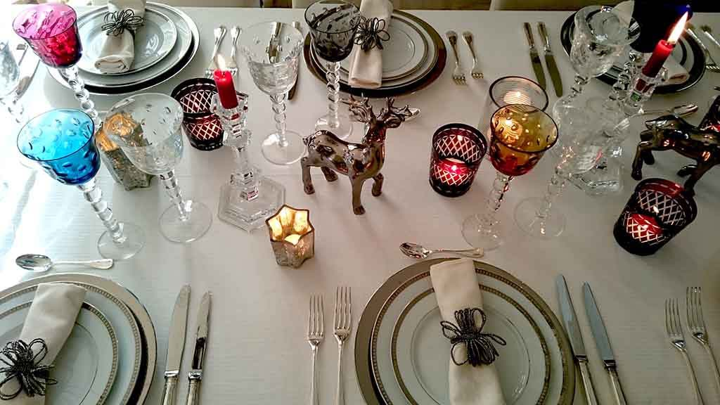 Partial view from atop of a beautifully styled tabletop for a New Year's Eve dinner party with lots of colored wine glasses, white porcelain plates with silver trims, silver cutlery all on a white tablecloth.