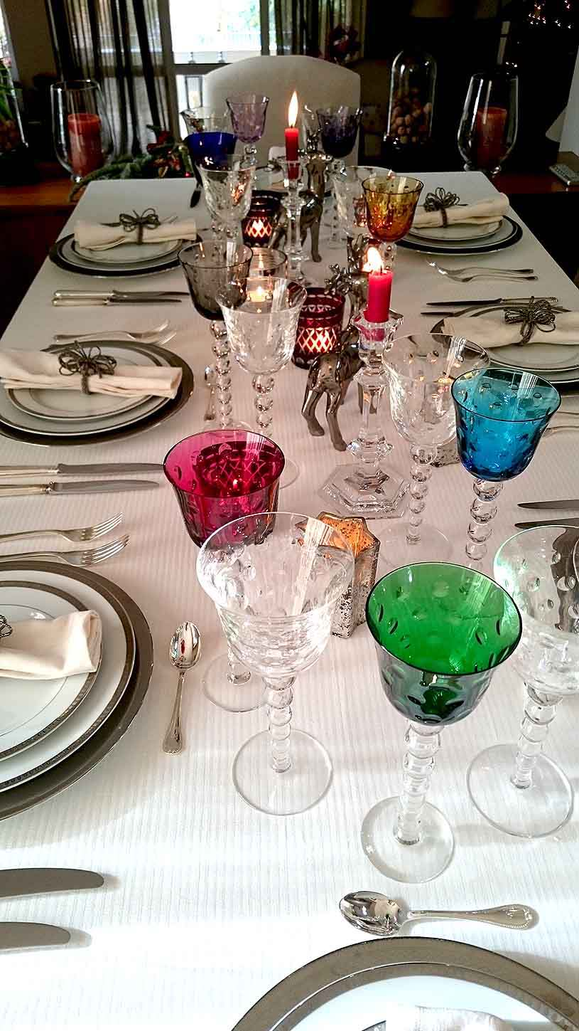 Another view of a beautifully styled tabletop for a New Year's Eve dinner party with lots of colored wine glasses, white porcelain plates with silver trims, silver cutlery all on a white tablecloth.