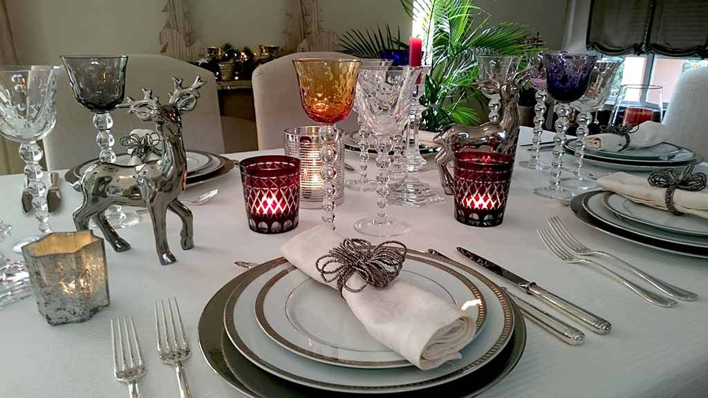 A beautifully styled tabletop for a New Year's Eve dinner party with lots of colored wine glasses, white porcelain plates with silver trims, silver cutlery all on a white tablecloth.