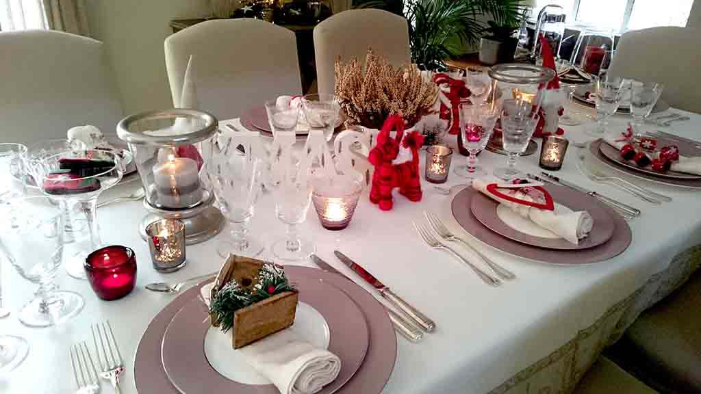 A stylish dinning table with tabletop Christmas decor, lots of candles, a small white planter pot with a Heather in it, a decorative XMAS sign and lots of red splashes. Atop every guest's napkin at each place setting, there is a different Christmas ornament - a small gift for each guest.