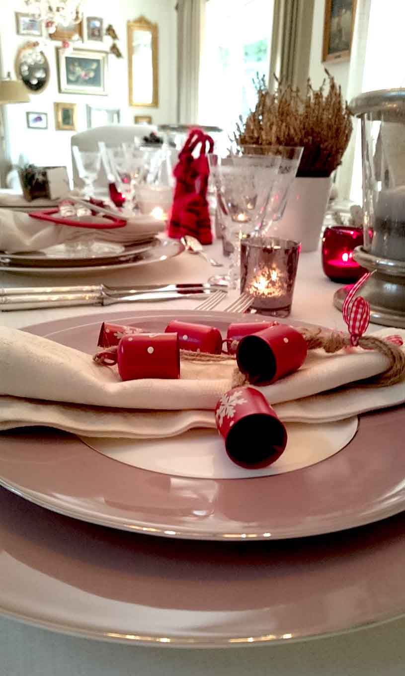 Detail of a place setting from the side of a stylish dinning table with tabletop Christmas decor, lots of candles, a small white planter pot with a Heather in it, a decorative XMAS sign and lots of red splashes. Atop every guest's napkin at each place setting, there is a different Christmas ornament - a small gift for each guest.