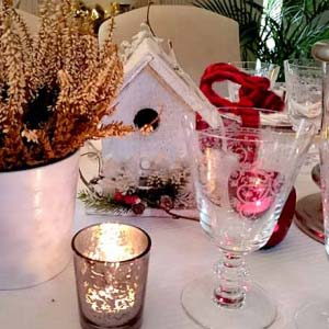 View from above of a a stylish dinning table with tabletop Christmas decor, lots of candles, a small white planter pot with a Heather in it, a decorative XMAS sign and lots of red splashes. Atop every guest's napkin at each place setting, there is a different Christmas ornament - a small gift for each guest.