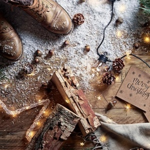 A flatlay with a pair of brown boots, timber logs, nuts and a string of lights on a wooden floor with sprinkles of snow. Image shot by Oliver Perrott for Lights4Fun.co.uk.