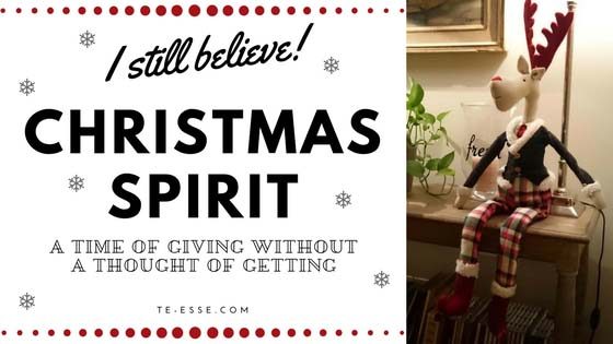 a graphic with an image of a reindeer dolly dressed in a holiday outfit sitting up on a sideboard against a table lamp in Elisabeth's home. On the left there's some writing: I still believe! Christmas spirit a time of giving without a thought of getting!