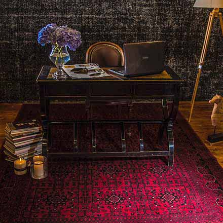 A classic black wooden desk with a tanned leather swivel chair resting upon a deep red bukhara area rug. There's also a stack of books on the left with lit candles and a floor lamp on the right. A glass vase with flowers is on the desk along with a laptop and a newspaper. The background wall is dark gray.