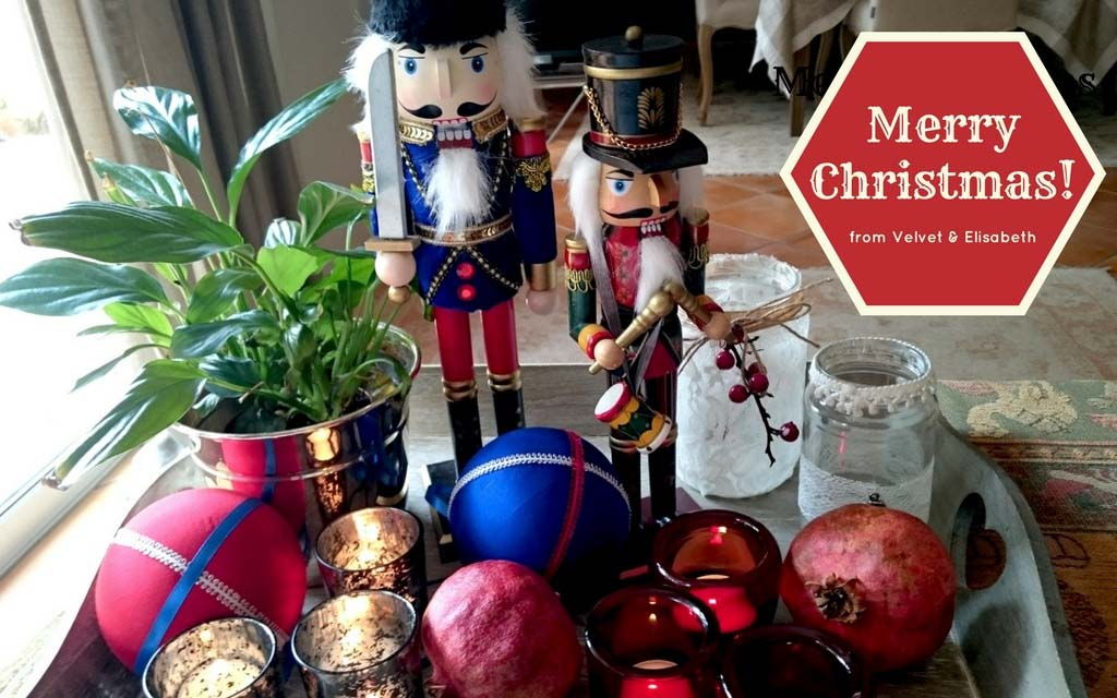 Two nutcrackers as decor in a tray between a planter pot, large colorful baubles, a pomegranate (for good luck), and candles. On the top right corner, there is a sign saying Merry Christmas from Velvet and Elisabeth