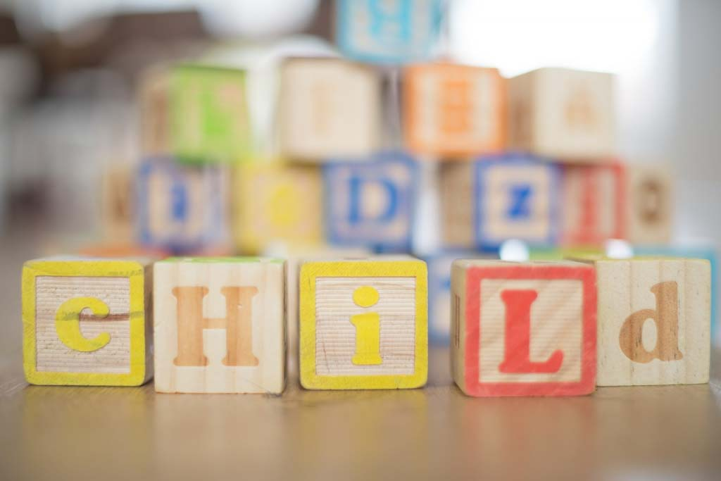 Wooden building blocks with letters on them. In the foreground five such blocks spell out the word child.