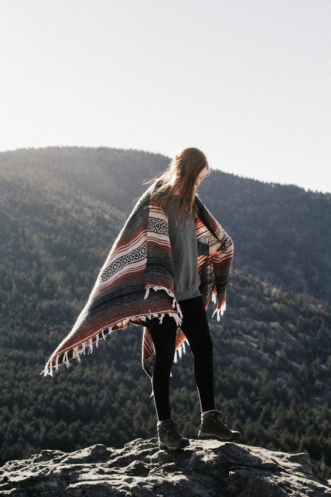 Woman on top of a rocky hill wear grey sweats with black leggings and hiking boots and covering herself with a patterned blanket.