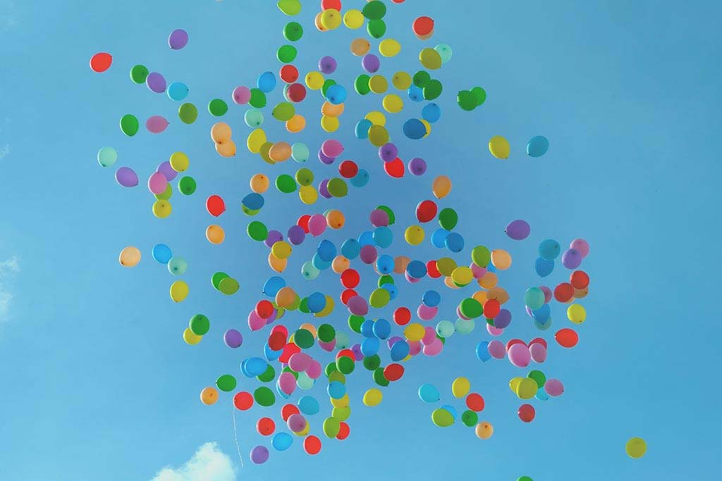 A big bunch of colorful balloons flying up into a blue sky. Let go of anything that holds you back. Let it all fly away!