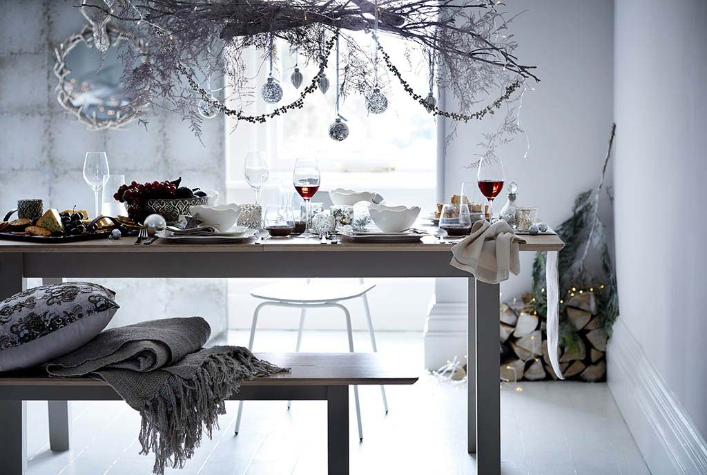 A minimal grey dining area, with a silver wreath decor hanging atop, a minimal sitting bench coordinated with the dining table