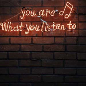 A neon sign on an exposed brick wall saying you are what you listen to.
