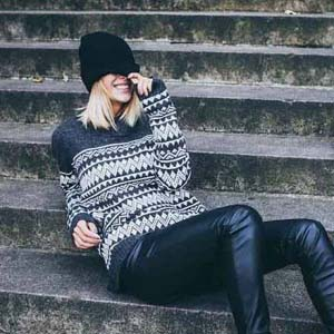 A blonde young woman with a hat on covering her eyes, is smiling while sitting on some concrete steps wearing a pattern sweater and black leather pants