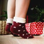 A little girl is on her toes wearing deep red ankle socks with white stars, as she apparently is reaching out to a Christmas tree with gift boxes under it