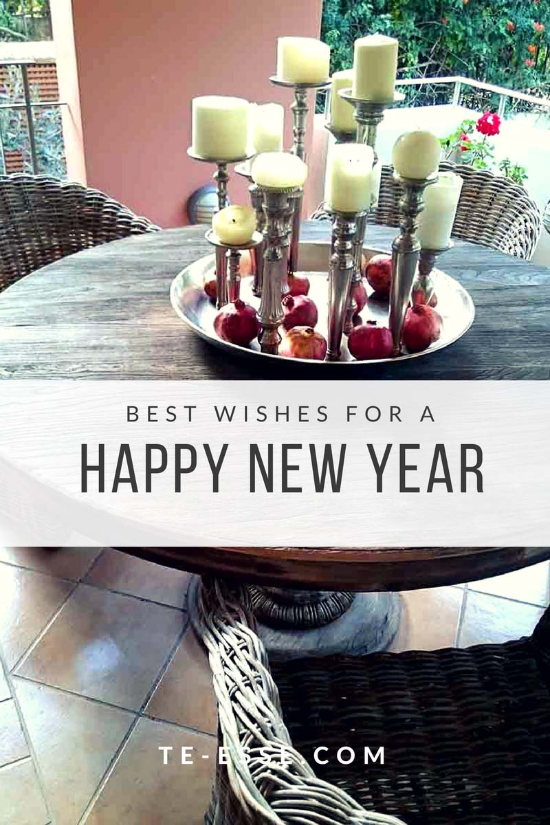 A rustic round dining table with rattan chairs outdoors in a balcony, with a large flat bowl with tall candlesticks and lots of pomegranates as a good luck charm. A white banner runs in the middle saying Best Wishes for a Happy New Year.