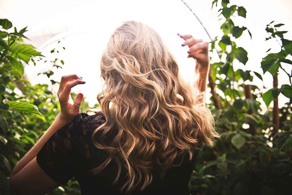 The rear of a young blonde woman with long hair walking in nature