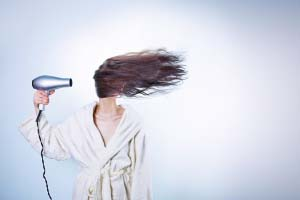A woman in a white bathrobe is blow drying her long hair