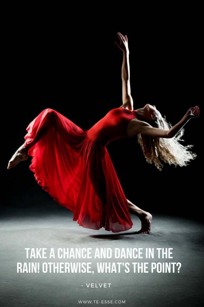 A superb photo by Patrick Kool of a woman in a long red dress dancing in a dark room. The quote under reads Take a chance and dance in the rain. Otherwise what's the point? cited from Velvet
