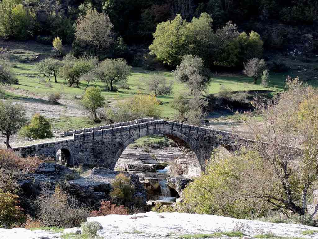 Another view of a beautiful old stone arched bridge over a stream of water in nature.