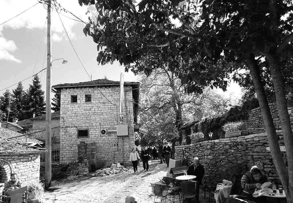 A black and white image of a village's path with stone and slate houses, people walking down the path or resting in the sitting areas of a cafe bistro.