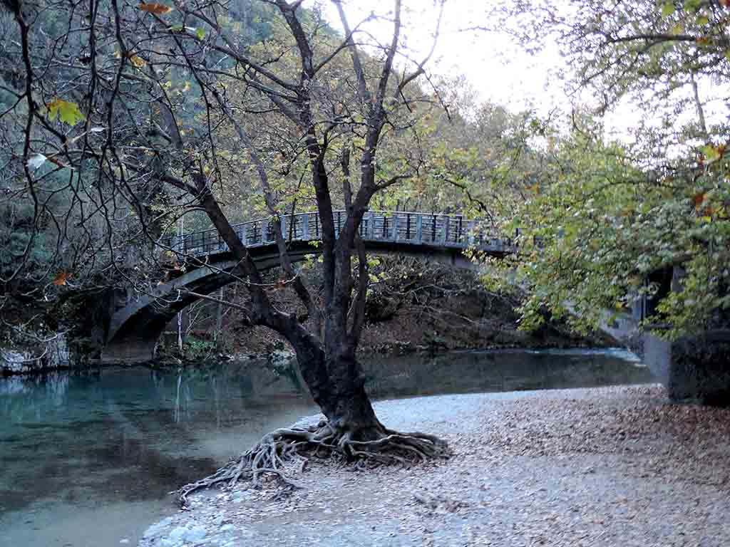 Another view of a beautiful stone bridge over clear blue river waters in the Voidomatis - Aoos National Park