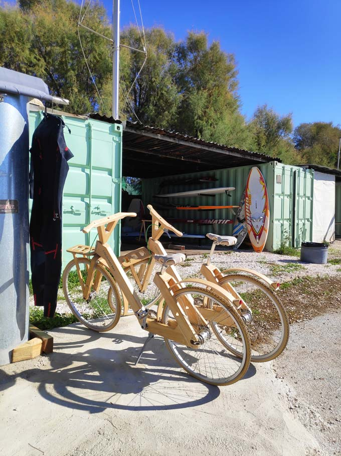 Two retro looking bikes parked by a shed where surf boards are stored. Image by Velvet.